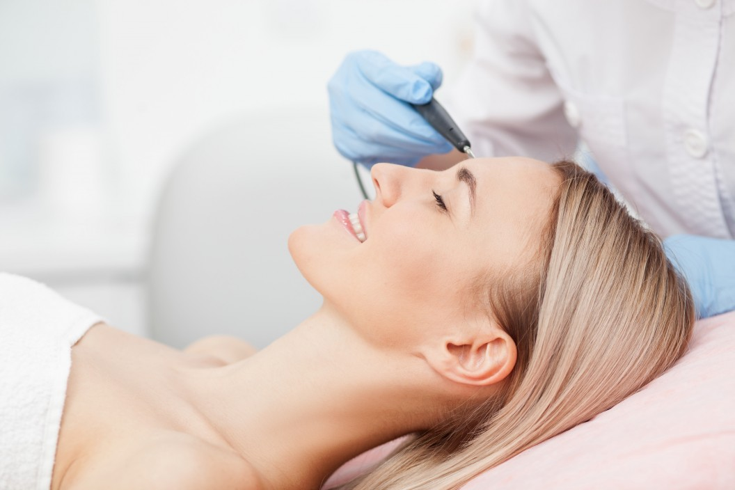 Close up of arms of experienced beautician performing laser skin treatment of skin on female face. The young woman is lying and smiling